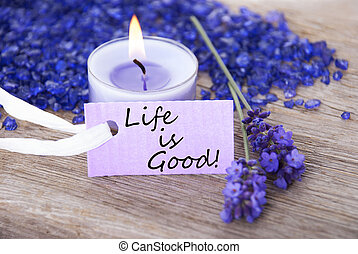 Purple Label With Candle Light And Lavender Blossoms With English Life Quote Life Is Good Wooden Background With White Ribbon
