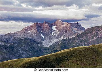 Purple light illuminates a big mountain and the moody sky -...