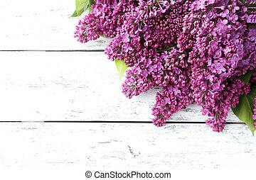 Purple lilac flowers on white wooden background
