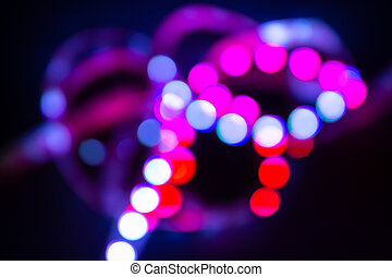 Purple Neon bokeh lights on black. Abstract blurred background