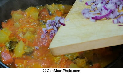 Purple Onion is added to the vegetarian dish, stirring with a wooden spoon.