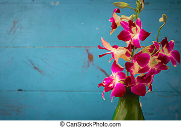 Purple orchid flowers in green vase with wooden wall