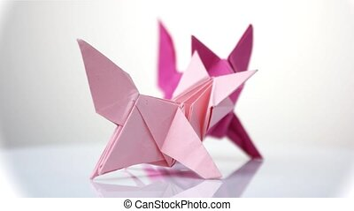 Purple origami foxes. White isolated background. Origami...