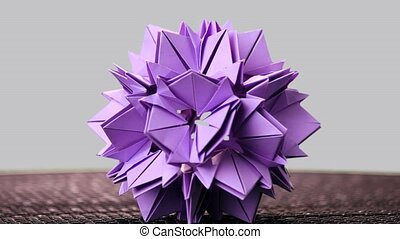 Purple origami sharp ball exposition. Rotation. Grey...