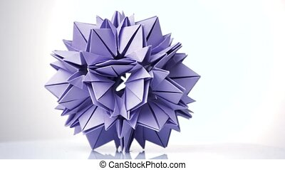 Purple origami transforming spiky ball. Bright isolated...
