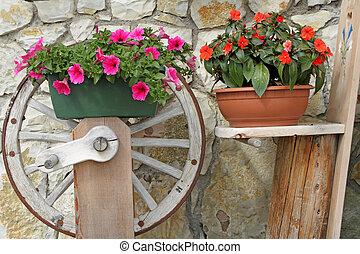 purple petunia and red impatiens in rustic pots