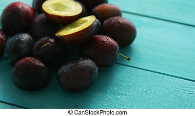 Purple plums on blue wood - From above shot of pile of...