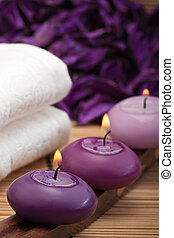 purple candles with white towel in spa setting