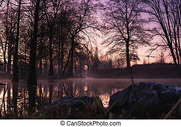 Purple sunset over lake with reflections