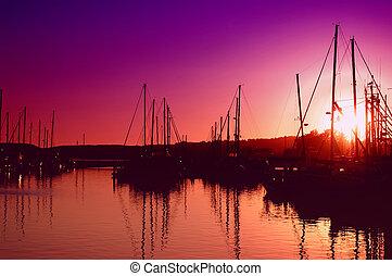 Sun setting behind an oceanfront marina