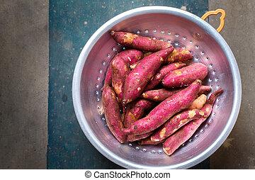 Purple sweet potato in a metal colander