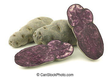 purple truffle potatoes and a cut one on a white background