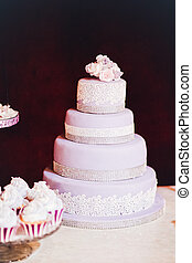 Purple wedding cake with a rose on the table