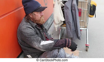 Purposeless existence - Bearded vagabond sitting by the cart...