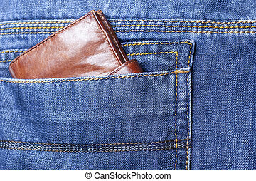 Purse or wallet in the back pocket of blue jeans.Close up.
