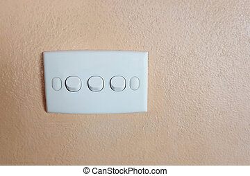 Push button of white switch on orange wall.