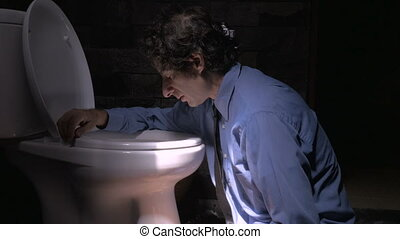 Push in of a man feeling ill or depressed while leaning up against a toilet