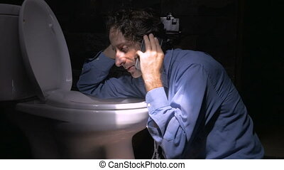 Push in of a man sitting on the floor against a toilet on a phone