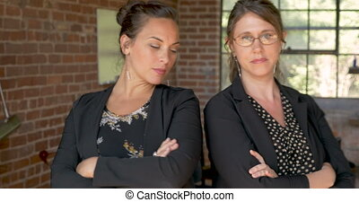 Push in of two serious women with arms crossed looking at camera