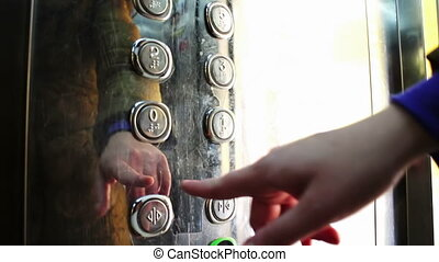 Push on the button in an elevator and lift movement - The...