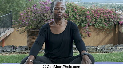 Push out of an attractive African American senior woman meditating