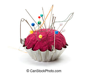 Push pins, needles and safety pins clustered in pincushion