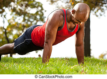 Push Up - A man doing a push up in a park