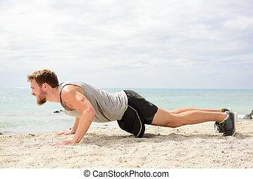 Push-ups - man fitness exercising on beach