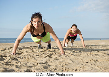 Push ups on a beach - Two women doing pushups on a beach...