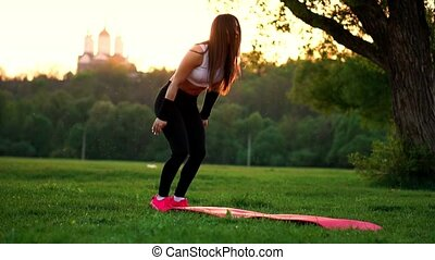 Push ups or press ups exercise by young woman. Girl working out on grass crossfit strength training in the glow of the morning sun against a white sky with copyspace. Caucasian model.