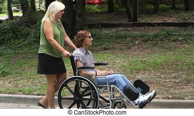 Daughter pushes invalid mother in wheelchair outside on the street.