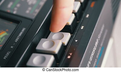 Pushing Play Button on a Vintage Tape Recorder. Close-up. Pushing a Finger Button Play. Man finger presses playback control buttons on audio cassette player. Macro. Transistor retro radio.