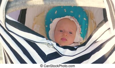 Pushing the pram with baby girl - Baby girl in bonnet lying...