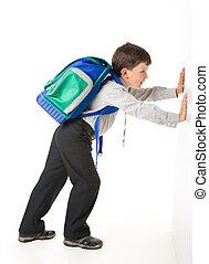 Pushing wall - Image of schoolchild with backpack pushing...