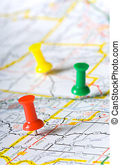 primary colored pushpins marking specific spots on a map