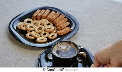 Put a cup of coffee on the table. There is a plate with...