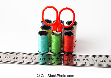 Put a scissors in a Multicolor sewing threads and ruler on white background