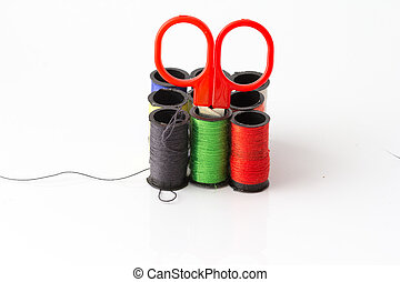 Put a scissors in a Multicolor sewing threads on white background