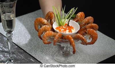 Put on the table a dish of shrimp. Slow motion - Put on the...
