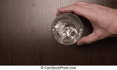 Put on the table a glass with ice cubes, top view