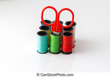Put scissors in a Multicolor sewing threads on white background