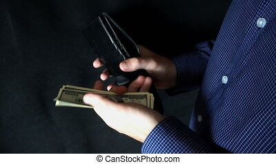 puts money in wallet. A man opens a leather purse and puts bills