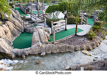 Miniature golf course showing multiple playing holes and a river running through it