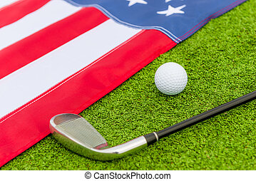 putter and ball lie on the grass near to a flag of America