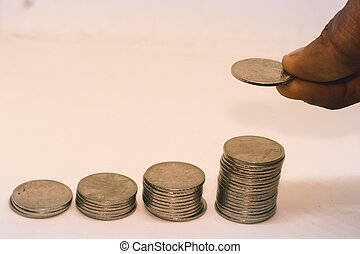 Putting a coin over a stack of coins. Isolated on white background. Concept of money management