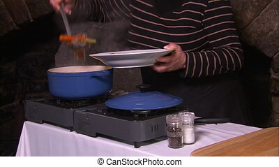 Putting a dish on a plate - A woman prepares a food on a...