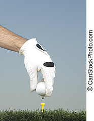 putting a golf ball in the tee