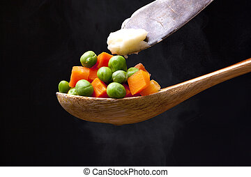 Putting butter on peas and carrots.