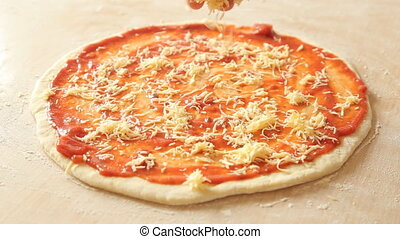 Putting cheese topping on pizza dough already coated with tomato sauce.