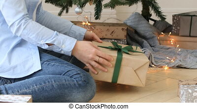 Putting Christmas gifts under a holiday tree